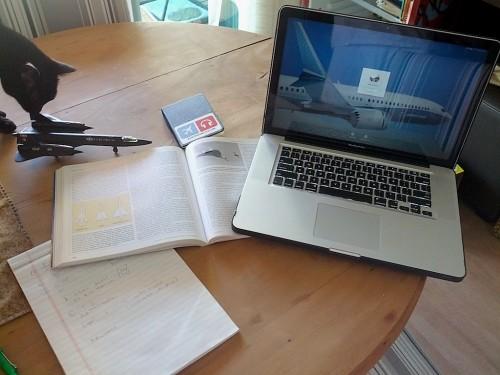 Mesa com notebook e livro de pesquisa